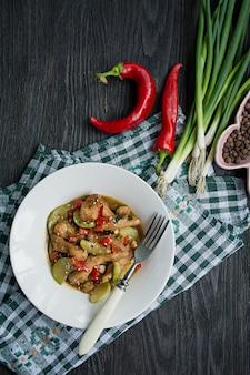 Insalata calda con pollo, zucchine e peperoncino, cosparsa di semi di sesamo ed erbe. cibo asiatico. legno scuro.