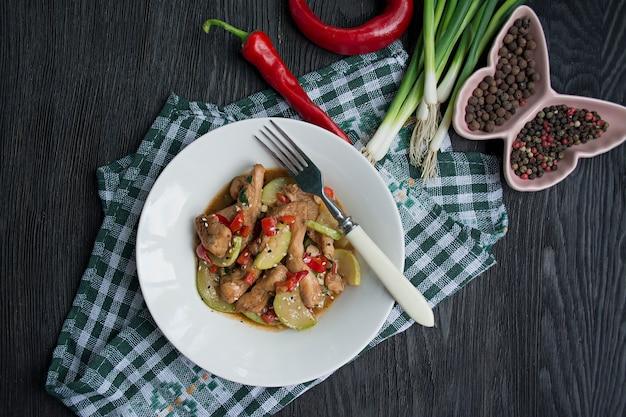Insalata calda con pollo, zucchine e peperoncino, semi di sesamo ed erbe aromatiche.