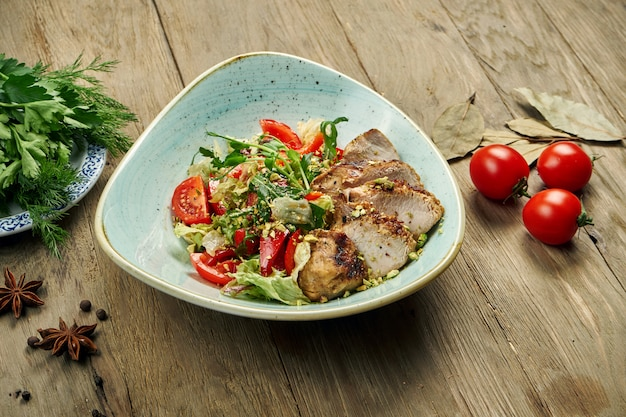 Insalata calda con tacchino grigliato, pomodori, pistacchi, lattuga in una ciotola blu su un tavolo di legno. dieta sana
