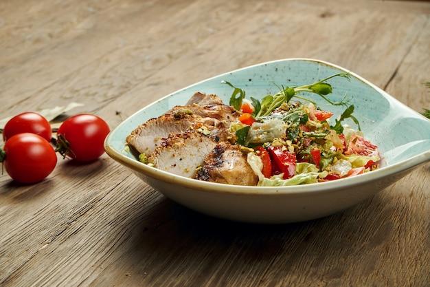 Insalata calda con tacchino grigliato, pomodori, pistacchi, lattuga in una ciotola blu su una superficie di legno. dieta sana