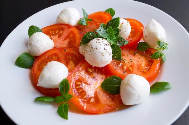 Insalata caprese con pomodori maturi e mozzarella con foglie di basilico fresco. cibo italiano.