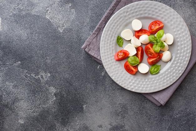 Insalata caprese di pomodori, mozzarella e basilico. cucina italiana. copia spazio