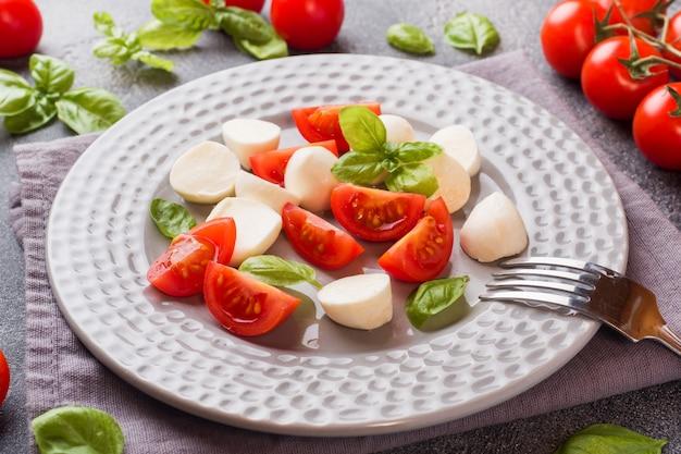 Insalata caprese di pomodori, mozzarella e basilico su uno sfondo scuro. cucina italiana.