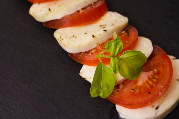 Insalata caprese italiana con alternanza di fette di pomodoro e mozzarella condite con pepe e foglie di basilico fresco