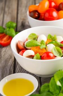 Insalata caprese italiana con pomodorini, mozzarella e basilico fresco