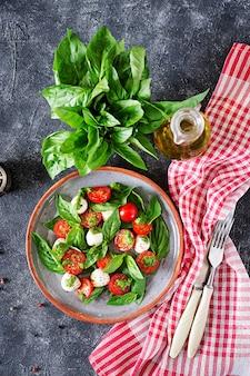 Insalata caprese. pasto sano con pomodorini, palline di mozzarella e basilico.