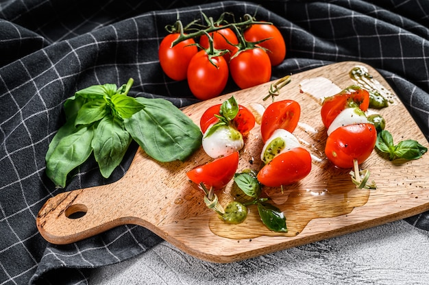 Insalata caprese su spiedino, pomodoro, pesto e mozzarella. merenda tartine. sfondo grigio. vista dall'alto