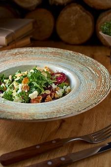 Insalata con barbabietola rossa, formaggio feta, rucola e condimento piccante su fondo rustico. cibo sano.