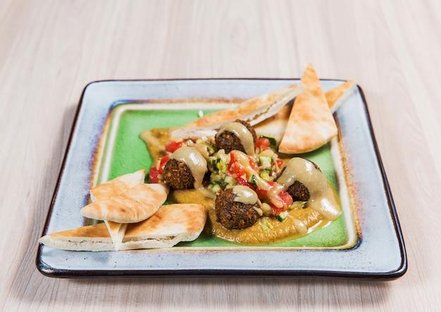 Insalata con carne e verdure in lamiera quadrata sul tavolo in legno chiaro. cibo salutare
