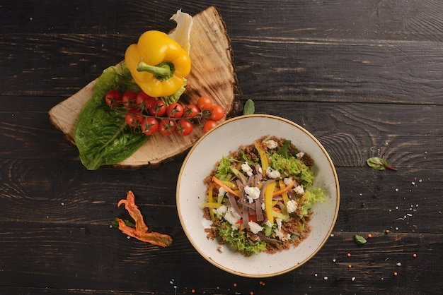 Insalata con carne, peperoni, lattuga e crema di formaggio. in un piatto bianco su un tavolo di legno. con decorazioni di verdure