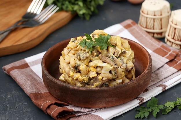 Insalata con fagioli, prezzemolo e funghi prataioli in una ciotola marrone