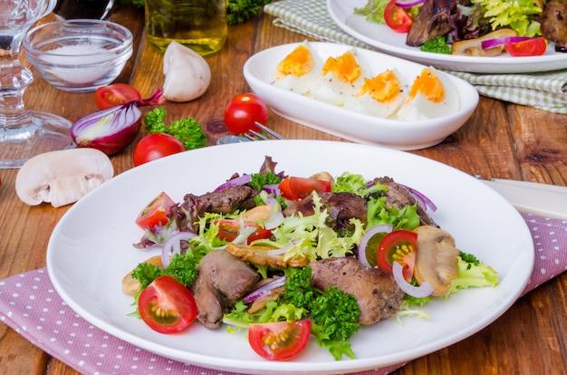 Insalata con fegato di pollo, funghi fritti e pomodori su un legno scuro.