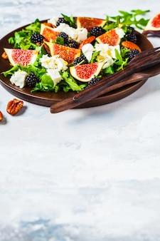 Insalata con fichi, feta e more in un piatto di legno su bianco