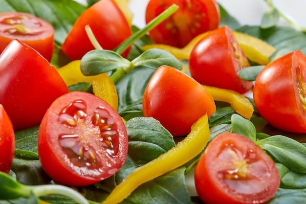 Insalata con foglie di basilico, pomodorini e peperone su un piatto bianco. primo piano, messa a fuoco selettiva