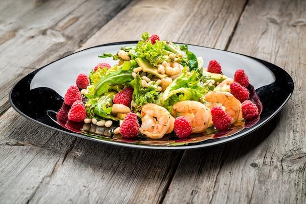 Insalata con gamberi, avocado e lamponi freschi, su un piatto nero.