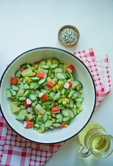 Insalata con mais, bastoncini di granchio, cetrioli in una ciotola bianca su sfondo bianco
