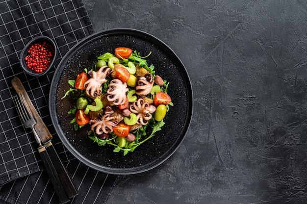 Insalata con polpo alla griglia, patate, rucola, pomodori e olive. sfondo nero. vista dall'alto. spazio per il testo