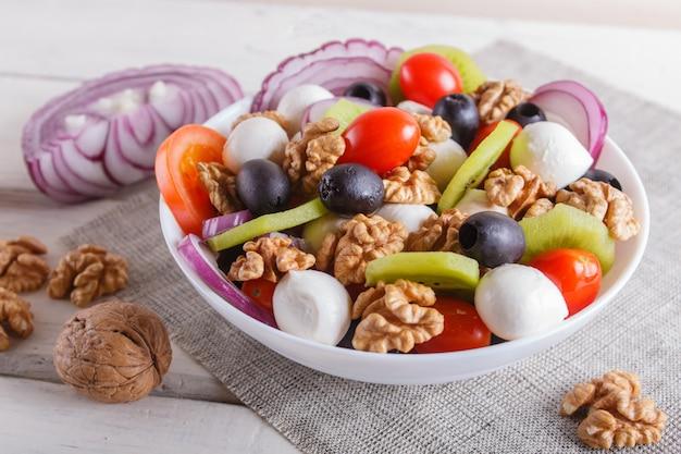 Insalata con pomodorini, mozzarella, olive, kiwi e noci su superficie di legno bianco.