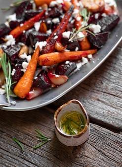 Insalata con rosmarino al forno delle carote della barbabietola su un fondo di legno