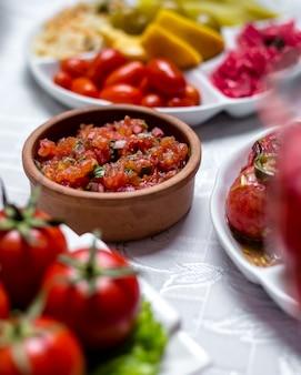Insalata del pomodoro con il basilico della cipolla di verdure nella vista laterale del piatto di argilla
