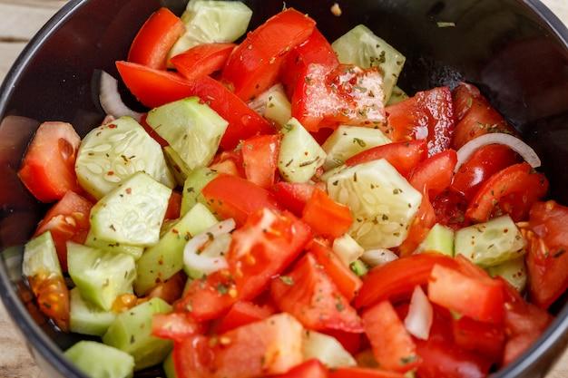 Insalata del pomodoro e del cetriolo in banda nera sulla tavola di legno