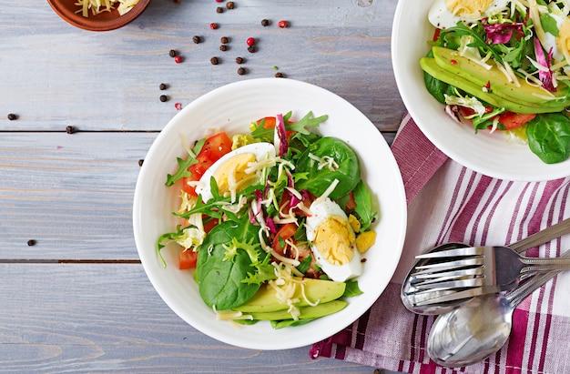 Insalata deliziosa e leggera di pomodori, uova e un mix di foglie di lattuga. colazione salutare. vista dall'alto
