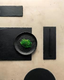 Insalata di alghe chuka, semi di sesamo nero, lastre di ardesia nera di diverse forme