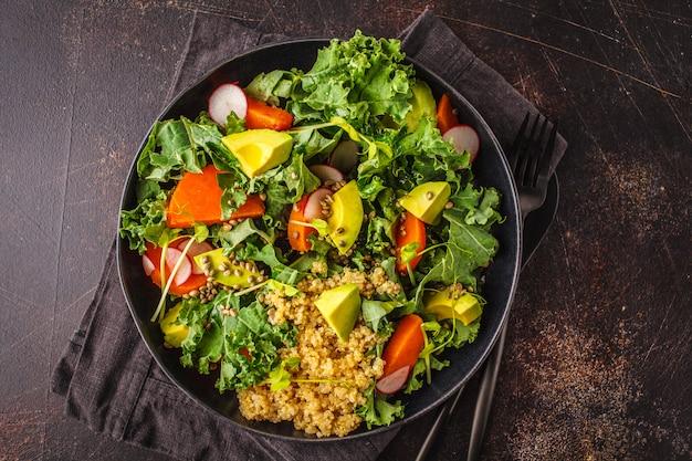 Insalata di avocado, quinoa, yam e kale in lamiera nera su uno sfondo scuro.