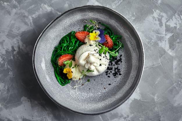 Insalata di burrata con fragole e alghe, su un grigio. insalata con formaggio buratta su un piatto grigio e marmo di cemento.