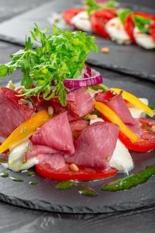 Insalata di cachi saporita fresca con rucola, prosciutto di parma, olio d'oliva ed erbe. autunno, inverno cibo sano