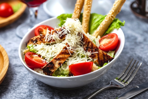 Insalata di caesar di vista laterale con lattuga e grissini di pollo alla griglia parmigiano