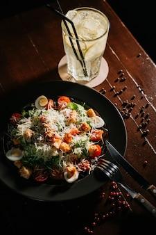 Insalata di caesar fresca in piatto bianco sulla tavola di legno scura. vista dall'alto copia spazio.