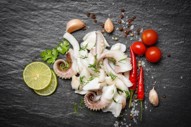 Insalata di calamari con erbe aromatiche al limone e spezie su sfondo scuro vista dall'alto tentacoli di polpo cucinato antipasto cibo piccante e piccante salsa di peperoncino frutti di mare cucinati serviti sulla piastra nera nel ristorante
