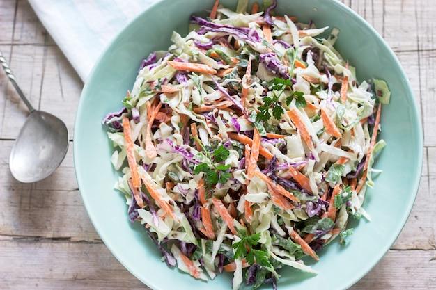 Insalata di cavoli di cavolo, carote e varie erbe con maionese in un grande piatto su un fondo di legno.