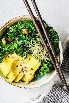 Insalata di cavolo con avocado e germogli in una ciotola, concetto di cibo vegano sano,