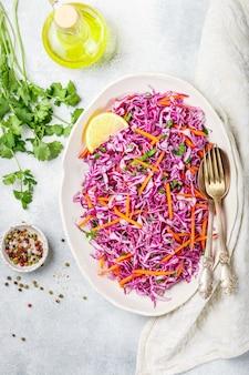 Insalata di cavolo rosso con salsa di carote, erbe e olio d'oliva e succo di limone. insalata di cavolo. cole slaw