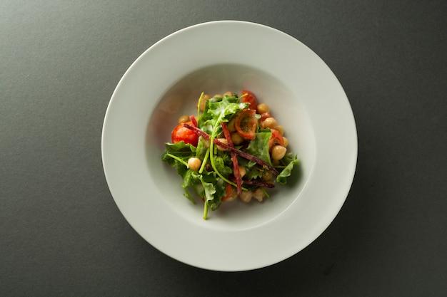 Insalata di ceci con verdure fresche - cetrioli, pomodori, barbabietole, spinaci.