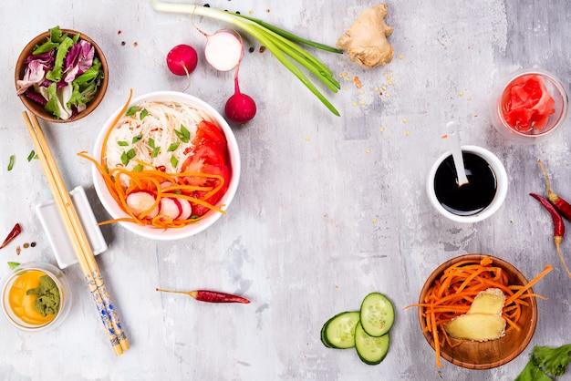 Insalata di cibo cinese, tagliatelle con verdure e noci su priorità bassa di pietra grigia