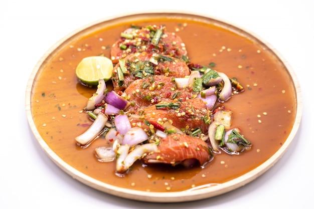 Insalata di color salmone piccante tailandese nell'isolato di legno del piatto su bianco.