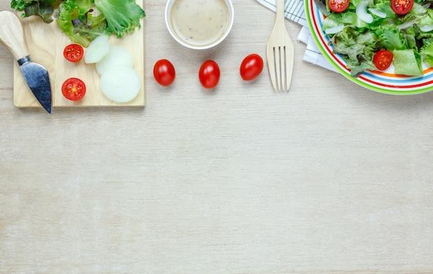 Insalata di cottura in vista superiore con salsa sul tavolo di legno con spazio di copia.