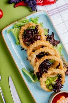 Insalata di erbe con anelli di cipolla fritti