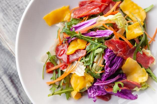 Insalata di estate fresca del primo piano con carne di bresaola, verdure, rucola, mango, carota, cavolo cinese.