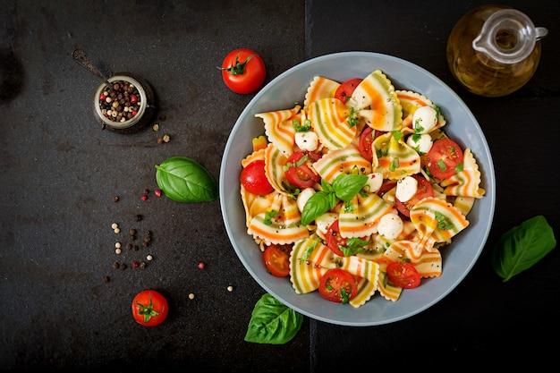 Insalata di farfalle di pasta colorata con pomodori, mozzarella e basilico.