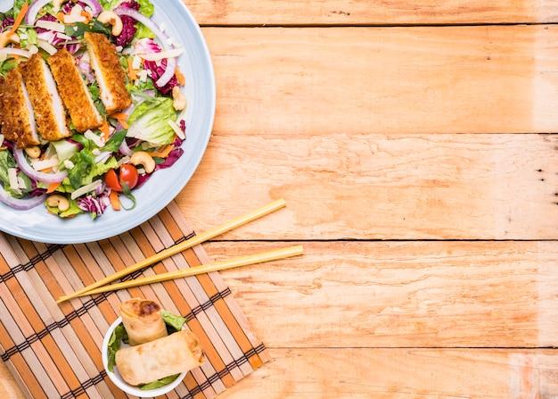 Insalata di filetto fritto con involtini primavera in ciotola di ceramica e bacchette contro tavolo in legno