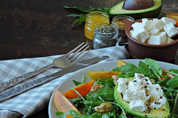 Insalata di fitness sano con rucola, avocado, feta e pomodorini gialli. ricetta per insalata con avocado, rucola e formaggio bianco. insalata vegetariana nutriente. dieta keto.