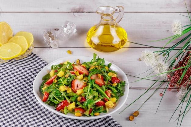 Insalata di fragole con rucola, mango e pistacchi con limone e olio d'oliva