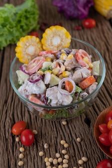 Insalata di frutta e verdura in una tazza di vetro su un pavimento di legno