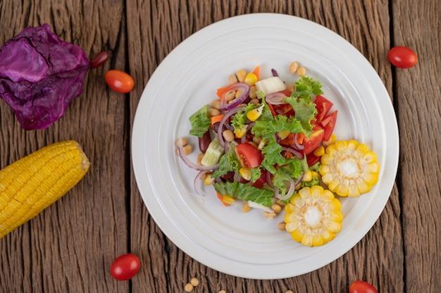Insalata di frutta e verdura su un piatto bianco su un pavimento di legno