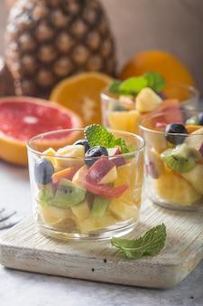 Insalata di frutta in bicchieri, cibi freschi d'estate, mirtilli di kiwi arancioni biologici sani, ananas, cocco. vista dall'alto