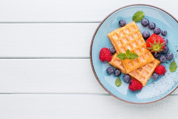Insalata di frutti di bosco freschi in un piatto su un tavolo di legno. appartamento laico, vista dall'alto, copia dello spazio.